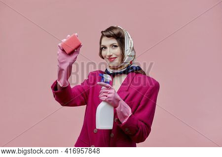 A Female Housewife Holds A Cleaning Spray And A Sponge. Bright Makeup.