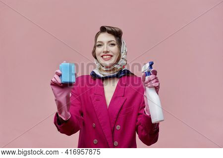 A Contented, Female Professional Cleaner Smiles And Looks At The Camera.