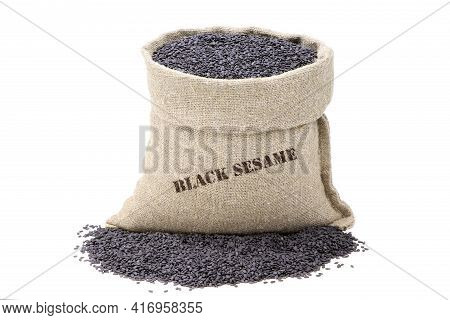 Seeds Of Black Sesame In A Sack Of Isolated On A White Background. Unpeeled Sesame Seeds. Black Sesa
