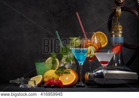 Hookah and cocktails set. Glasses with various cold  beverages, fruits, shisha and bar tool on dark grey background with copy space. Weekend or holiday party. Hookah bar, cocktail bar.