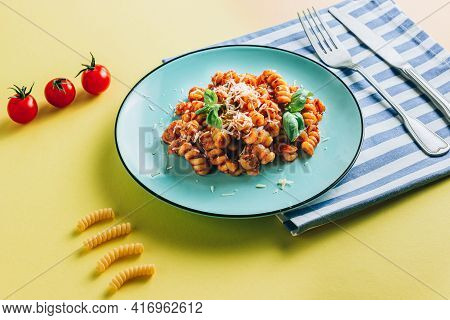 Plate Of Pasta, Tomato, Basil, Salt, Striped Napkin And Cutlery On A Yellow Background. Creative Com