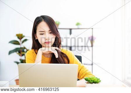 Asian Young Woman Seriously Working On Computer Laptop In House. She Thinking Find Solution Problem