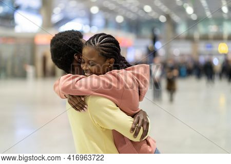 Family Reunion In Airport. Happy Black Male Hugging Excited Woman After Plane Arrival In Terminal. L