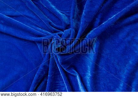 Colored Blue Textile Satin Fabric Folded In Folds And Waves With Highlights And Texture Shimmers In