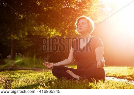 An Adult Woman In Dark Clothes In A Lotus Position Meditates In The Park In The Rays Of The Sun