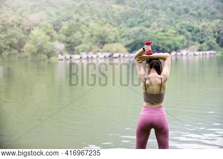 Rear View Of Female Fitness Instructor Exercising With Small Dumbbell On Green Grass Near Lake In Pa