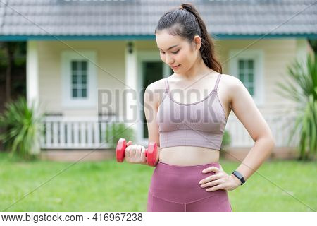 Female Fitness Instructor Exercising With Small Dumbbell On Frontyard.