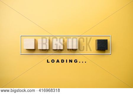 Wooden Blocks In Progress Bar With Loading Wording Under Bar On A Yellow Background. Loading Bar Pro