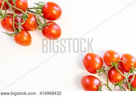 Branch Of Fresh Cherry Tomatoes Isolated On White Background With Copy Text In Middle