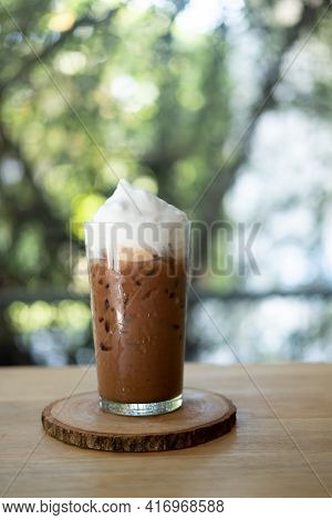 A Glass Of Iced Mocha Coffee With Milk Foam, Espresso Mixed With Chocolate Or Cocoa Topped With Milk