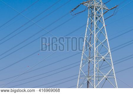 Pyeongtaek, South Korea; April 6, 2021: Asiana Airlines 747 In Blue Sky Behind Electrical Power Line