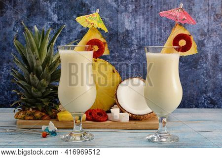 Pina Colada, Tropical Cocktail. Glass Of Pina Colada On A Blue Wooden Table With The Components Of T