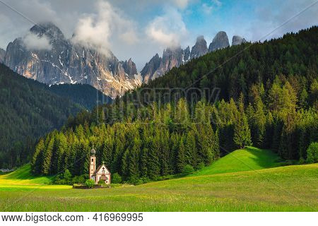 Great Travel Location, Cute Alpine St Johann Church In Val Di Funes Valley With Green Fields And Sno