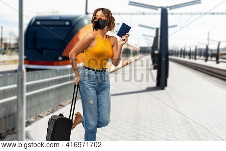 tourism, vacation and people concept - smiling young woman or teenage girl with travel bag and passport over train on railway station on background