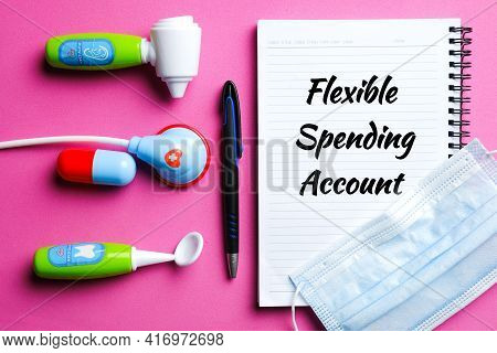 Flexible Spending Account On Notebook With Medical Toy And Face Mask. One Of A Number Of Tax-advanta