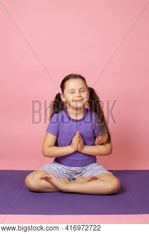 A Peaceful Happy Six-year-old Girl Does Yoga, Sits In A Lotus Position Or Prays, Isolated On A Pink
