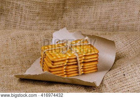 A Stack Of Rectangular Crackers Tied With String On Sackcloth. Close-up Of Crispy, Salty, Ready-to-e