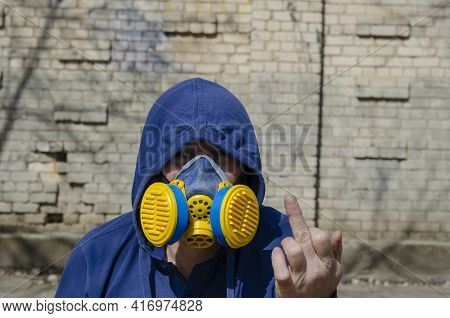 An Adult Unrecognizable Man Wearing A Respirator And Hood On Against A Brick Wall. A Middle-aged Man