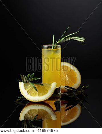 Traditional Homemade Lemon Liqueur Limoncello And Fresh Citrus On The Black Reflective Background. I