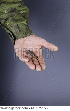 A Middle-aged Man's Hand With Automatic Rifle Ammunition On A Gray Background. One Cartridge Lying I
