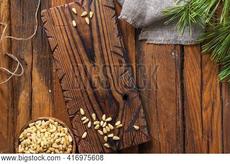 Still Life Cutting Board On The Table, A Round Bowl With Pine Nuts, Linen Cloth And A Pine Branch. T