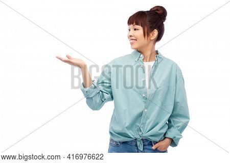 people and advertisement concept - happy asian young woman holding something imaginary on empty hand over white background