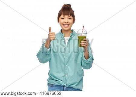 diet, healthy eating and detox concept - happy smiling young asian woman drinking green vegetable juice or smoothie from plastic cup with paper straw showing thumbs up over white background