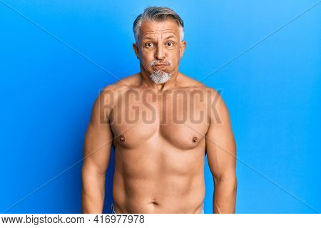 Middle age grey-haired man standing shirtless puffing cheeks with funny face. mouth inflated with air, crazy expression.