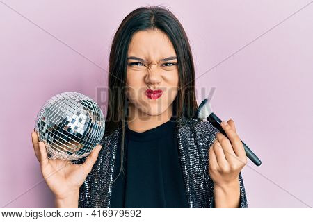 Young hispanic girl holding shiny disco ball and makeup brush puffing cheeks with funny face. mouth inflated with air, catching air.