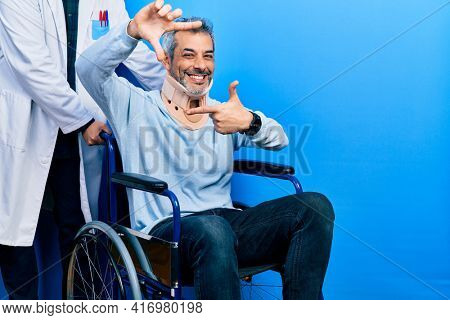 Handsome middle age man with grey hair on wheelchair wearing cervical collar smiling making frame with hands and fingers with happy face. creativity and photography concept.