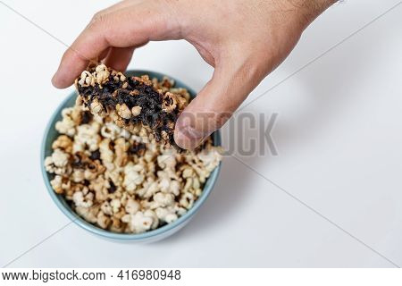 Spoiled Burnt Popcorn In A Blue Cup. Man's Hand Close Up