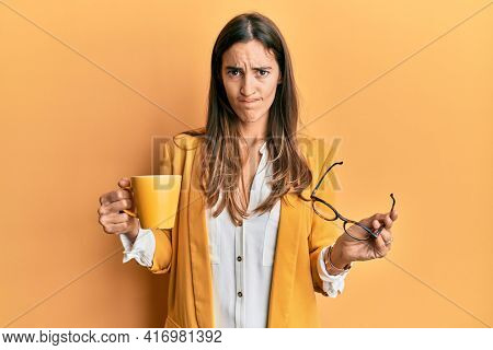 Young beautiful woman wearing business style drinking cup of coffee skeptic and nervous, frowning upset because of problem. negative person.
