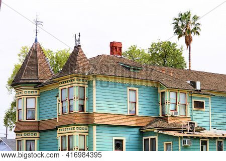 Historical Victorian House Besides Palm Trees Taken In A Residential Community