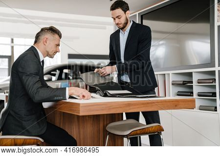 Salesman and client sitting at the desk in car dealeship, choosing new car