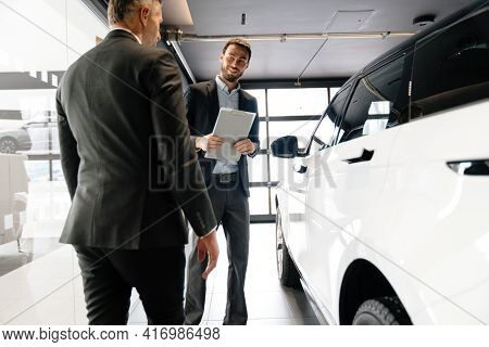 Male client choosing a new car in a car dealership, cosulting with a salesman
