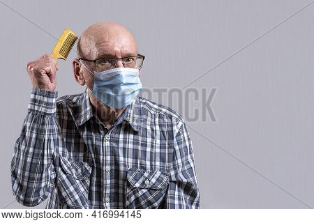 Old Bald Man With Glasses And Medical Mask With Hairbrush In His Hand. Copy Space.