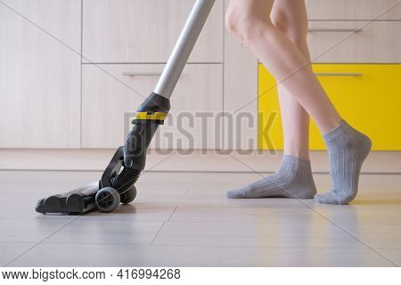 The Upright Vacuum Cleaner Cleans The Laminate Floor In The Kitchen. Women's Legs. Gray And Yellow T