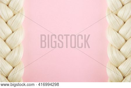 Two Beautiful White Pigtails. The Braid Is Braided By A Blonde In A Frame On A Pink Background. The