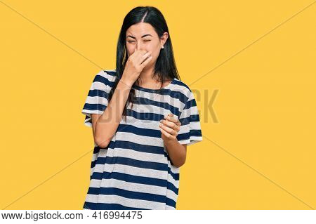 Beautiful young woman wearing casual clothes smelling something stinky and disgusting, intolerable smell, holding breath with fingers on nose. bad smell