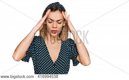 Young blonde girl wearing summer dress suffering from headache desperate and stressed because pain and migraine. hands on head.