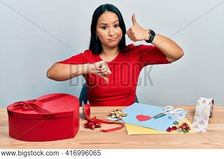 Beautiful hispanic woman with nose piercing doing handcraft creative decoration doing thumbs up and down, disagreement and agreement expression. crazy conflict