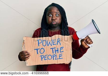 Young black woman with braids holding power to the people banner and megaphone puffing cheeks with funny face. mouth inflated with air, catching air.