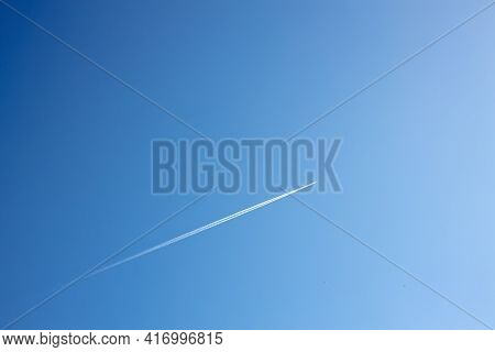 Fighter In Flight In The Air, White Reversing Trail Of The Aircraft In The Blue Sky, A Supersonic Fi
