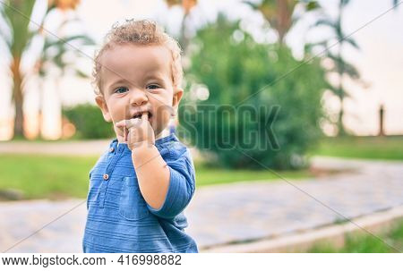 Sad little boy putting fingers on mouth touching gums because toothache at the park on a sunny day. Beautiful blonde hair male toddler in pain for new baby teeth outdoors