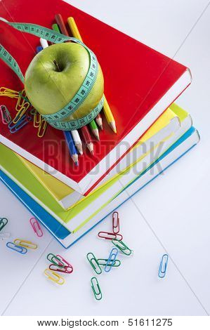 Green apple with measuring tape on colorful books