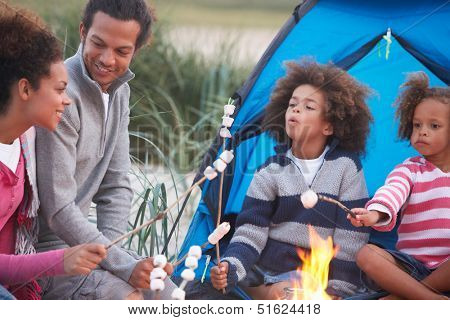 Family Camping On Beach And Toasting Marshmallows