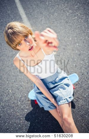 Trendy young woman pointing at camera sitting on her board