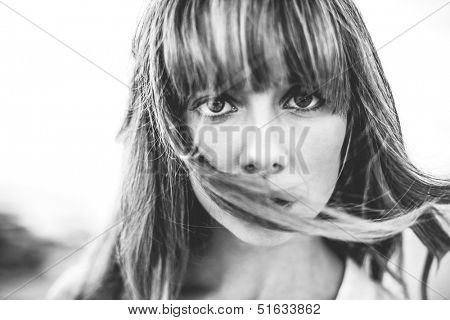 Hipster girl with fringe staring at camera in black and white artistic shot