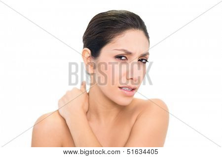 Wincing brunette touching her sore neck on white background