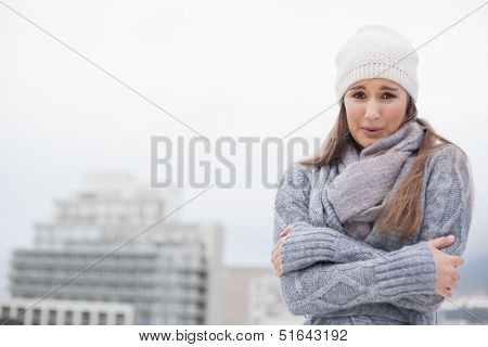 Shivering cute brunette with winter clothes on posing outdoors on a cold grey day poster